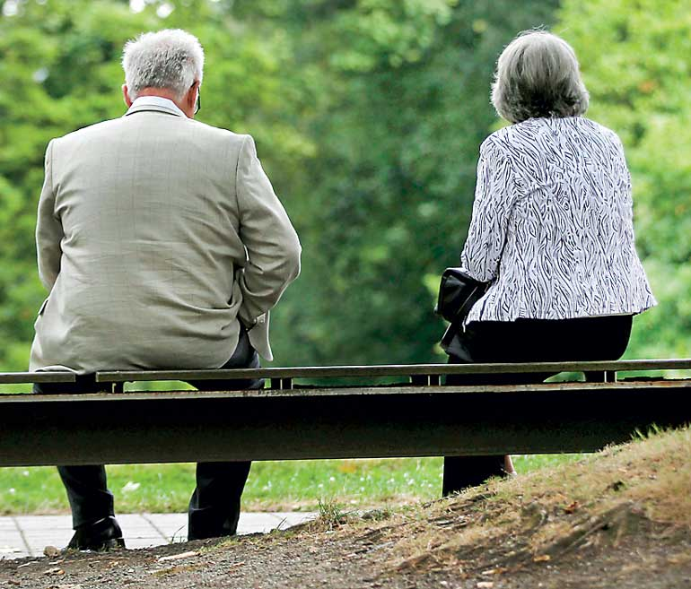 A man and a woman sit on a bench during a pause in the senior delegates meeting of the conservative Christian Democratic Union (CDU) in the western city of Recklinghausen